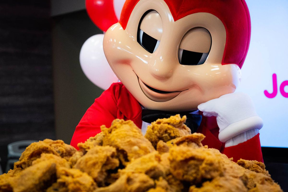 """The Jollibee mascot and and a bucket of its """"chickenjoy"""" fried chicken pieces."""