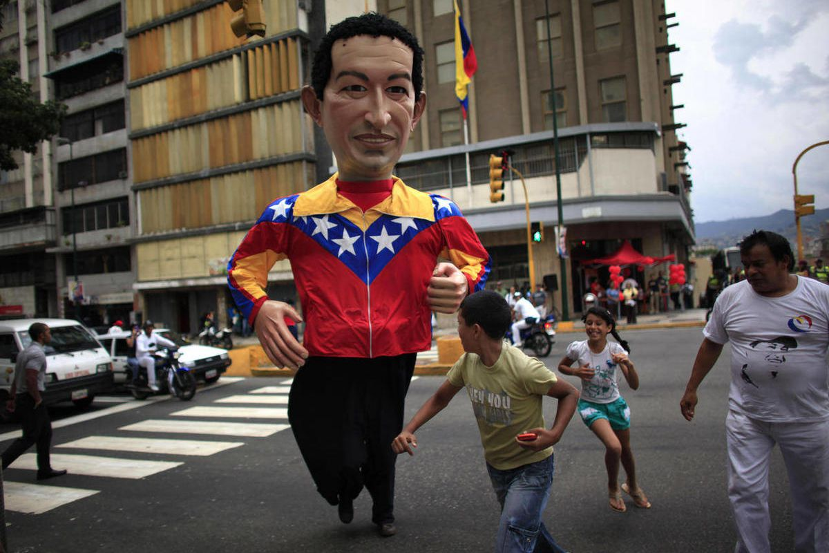 A person wearing a giant puppet depicting Venezuela's President Hugo Chavez crosses a street in downtown Caracas, Venezuela, Thursday, Sept. 27, 2012.  Venezuela's presidential election is scheduled for Oct. 7.