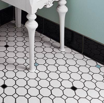 Mosaic tiled bathroom floor with white, blue, and black tiles.