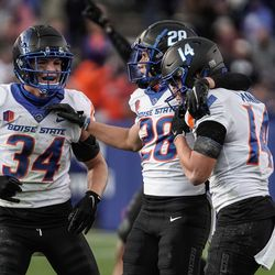 Boise State players celebrate a turnover as they compete against BYU during an NCAA college football game at LaVell Edwards Stadium in Provo on Saturday, Oct. 9, 2021.