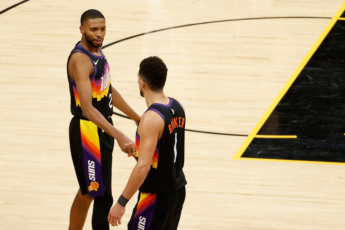 Mikal Bridges and Devin Booker of the Phoenix Suns celebrate defeating the Los Angeles Lakers in Game One of the Western Conference first-round playoff series at Phoenix Suns Arena on May 23, 2021 in Phoenix, Arizona.