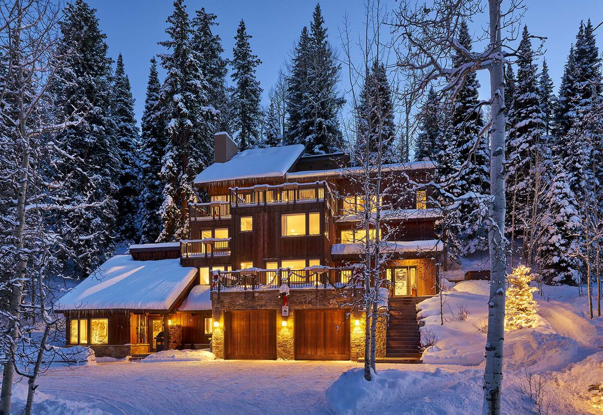 A wooden three-story house at dusk sits covered and snow with lights glowing gold. A forest surrounds the house.