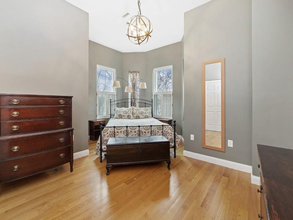 Bedroom with a bed nestled in a bay window next to a dresser.