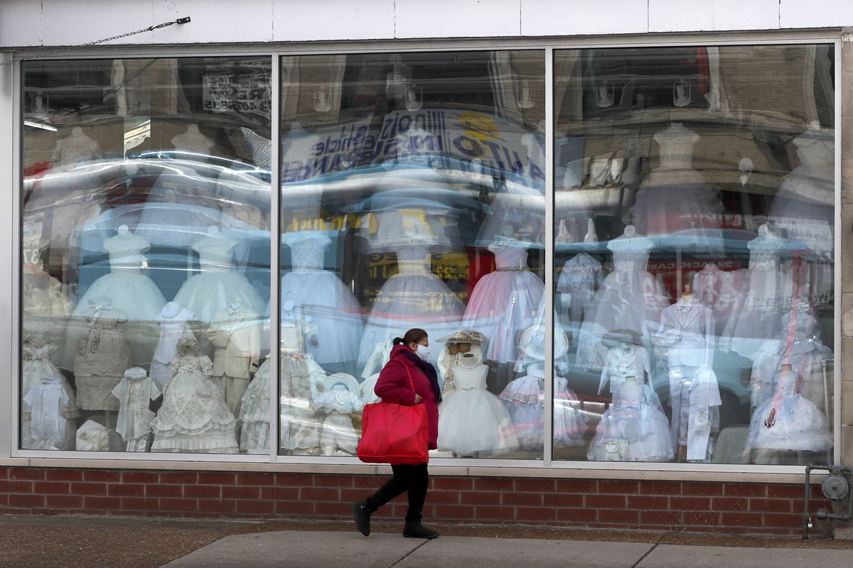 A woman wearing a protective mask walks past a closed children's clothing store in the Hispanic, Little Village in Chicago, Wednesday, April 15, 2020.