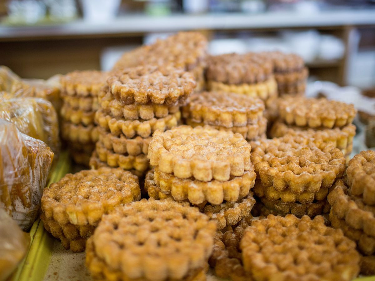 Wheel-shaped cookies in staacks on a counter dusted with granulated sugar.