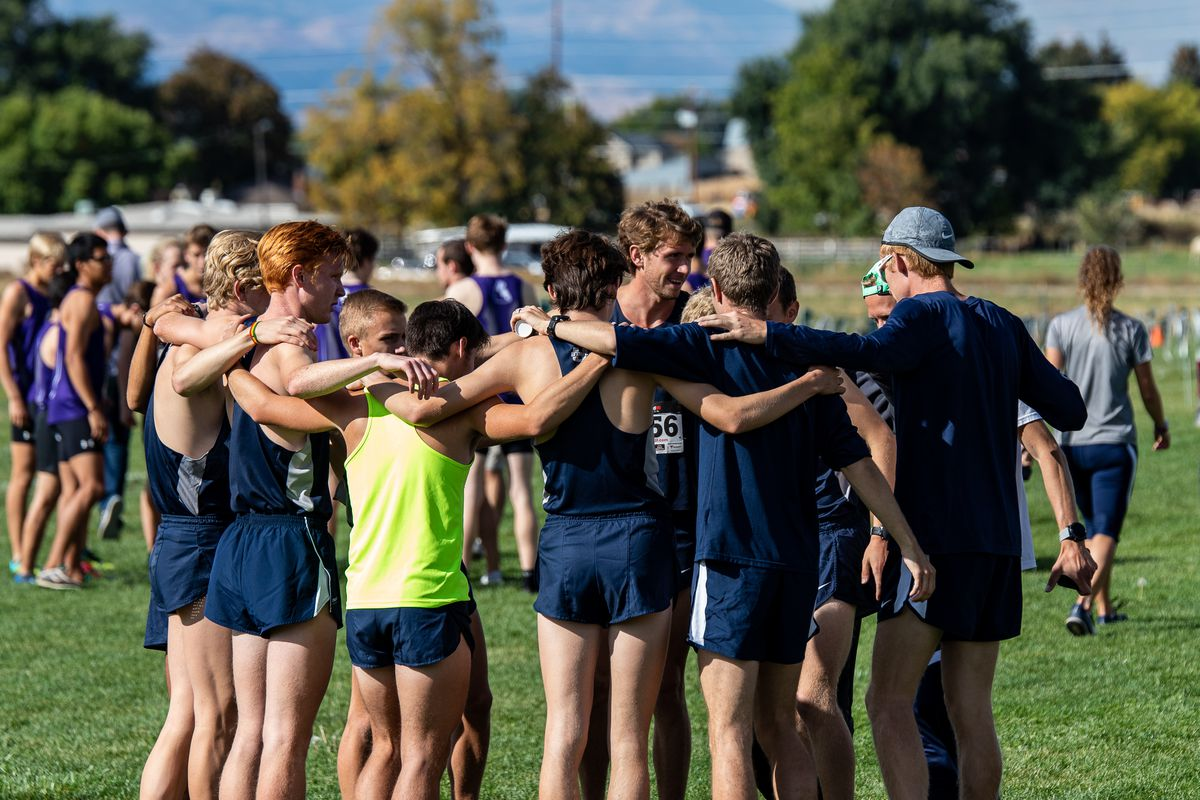 Aggie runners gather in a circle at the Steve T. Reeder cross-country meet.