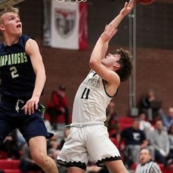 Alta's Hunter Humpherys goes to the hoop against Timpanogos' Jackson Holcombe in a boys basketball game at Alta High School in Sandy on Tuesday, Jan. 21, 2020.