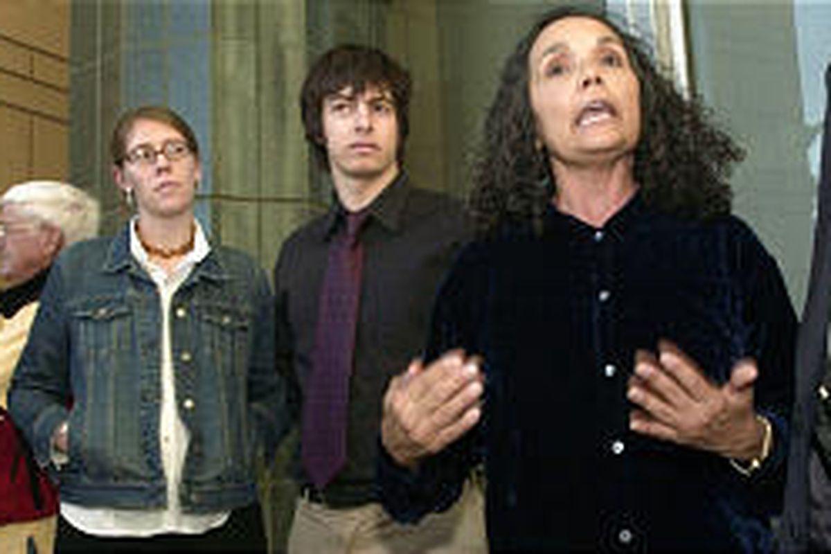 Shanti Sellz, at left in denim jacket, and Daniel Strauss, center, listen to attorney Isabel Garcia.