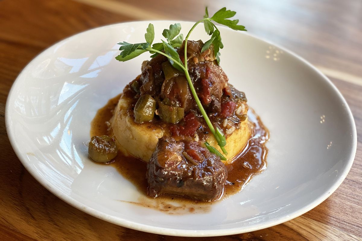 A closeup of oxtail and okra stew on a plate garnished with a sprig of parsley