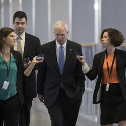 Sen. Ron Johnson, R-Wisc., center, who has expressed opposition to his own party's health care bill, walks to a policy meeting as the Senate Republican legislation teeters on the brink of collapse, at the Capitol in Washington, Tuesday, June 27, 2017. Senate Majority Leader Mitch McConnell, R-Ky., needs 50 members of his conference to back the GOP health care bill in order to pass it.