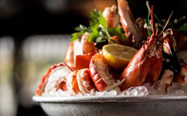 Closeup on a silver platter stuffed with ice and seafood