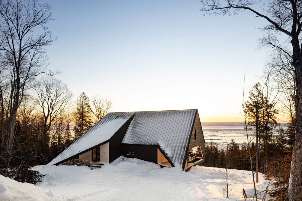 A snow-covered cabin looking out to a river.