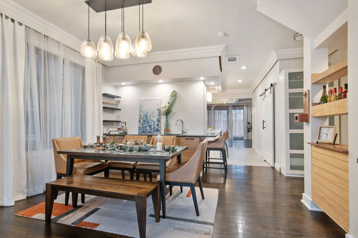 A dining room with a glass pendant light fixture, a table with chairs and a bench, and a built-in bar.