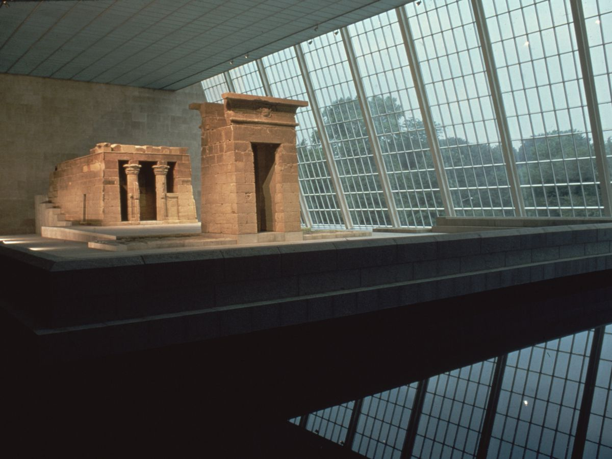 The Temple of Dendur at the Metropolitan Museum of Art. There are multiple historic buildings within a room with walls that have floor to ceiling windows.