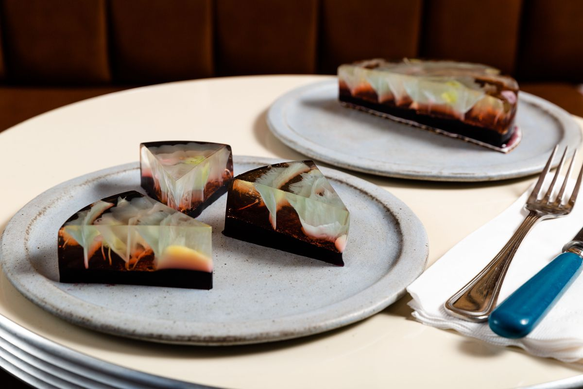 Three slices of the Boozy Cosmos cake sit on a gray plate next to silver ware.