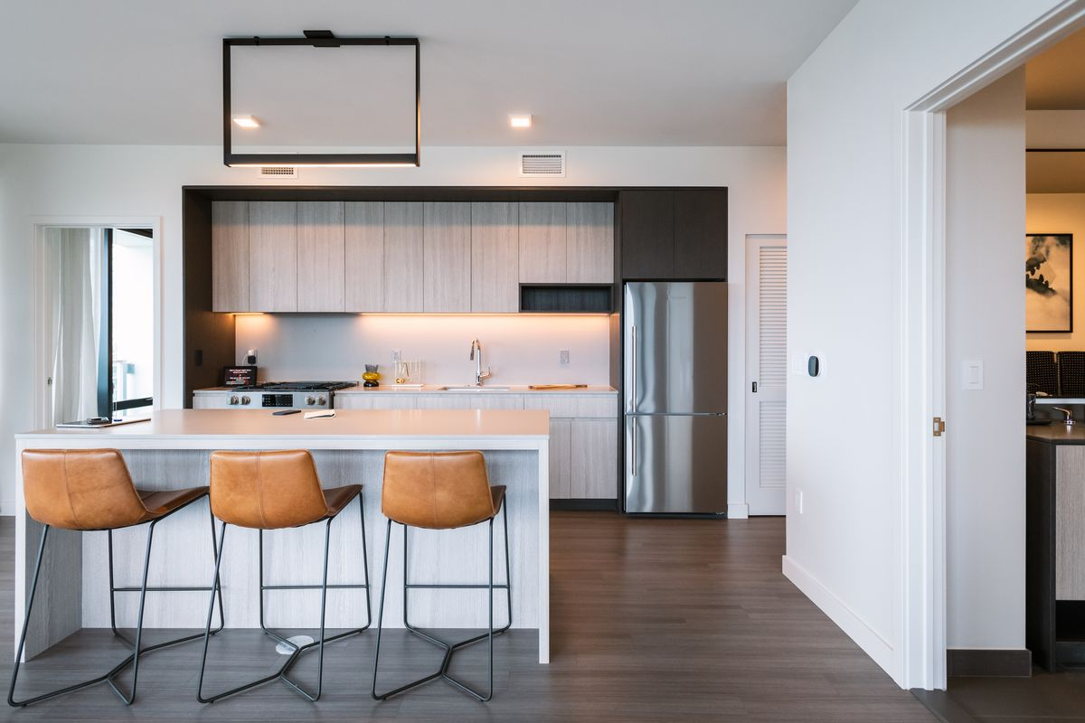 An open floorplan apartment with hardwood floors and an island breakfast bar with three stools.
