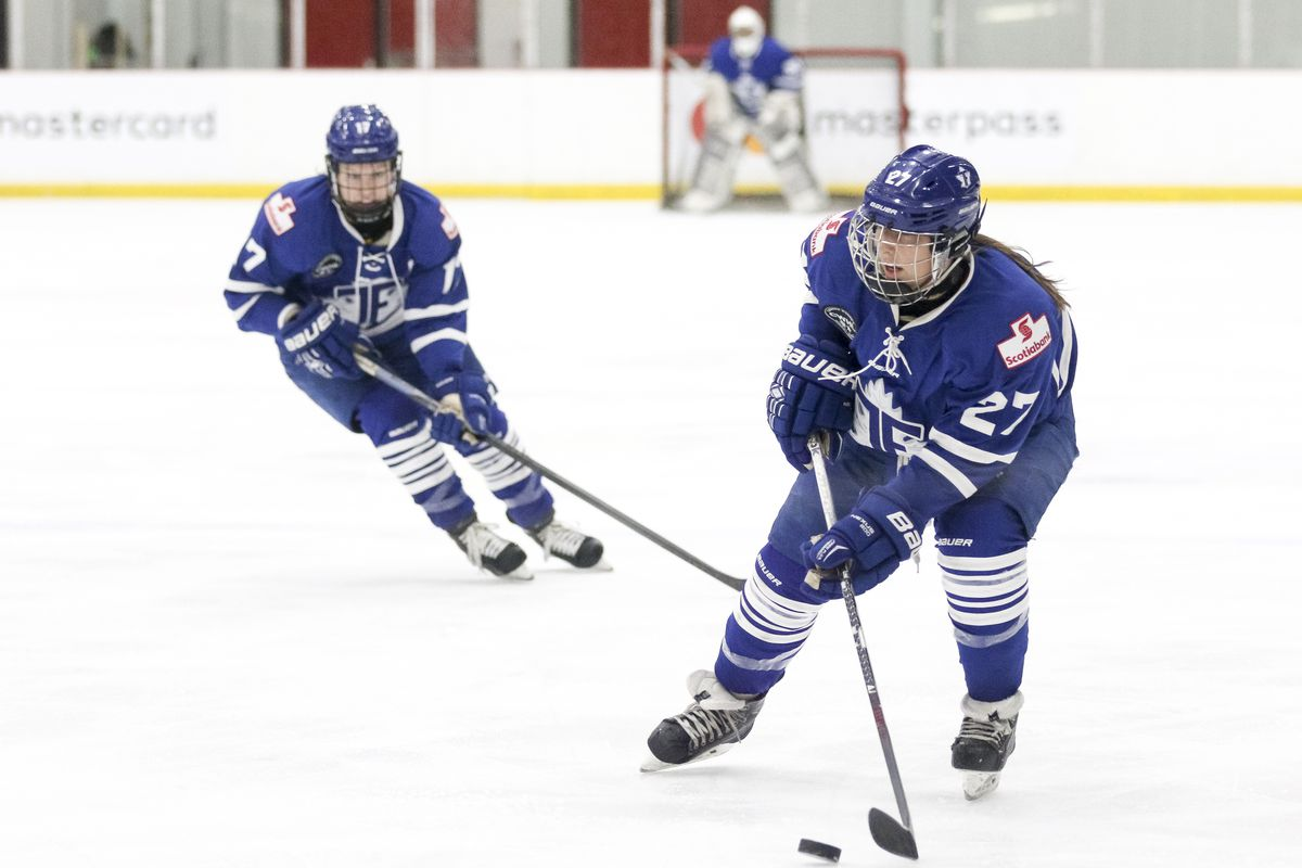 Carolyne Prévost in the foreground with the puck and teammate Emily Fulton trailing behind. Both wearing their blue home uniforms.