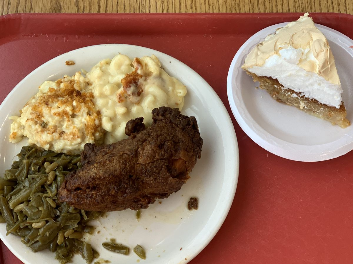 A red cafeteria tray on a wood table. Left plate topped with dark fried chicken, greens, cauliflower casserole. Right plate has slice of chess pie.
