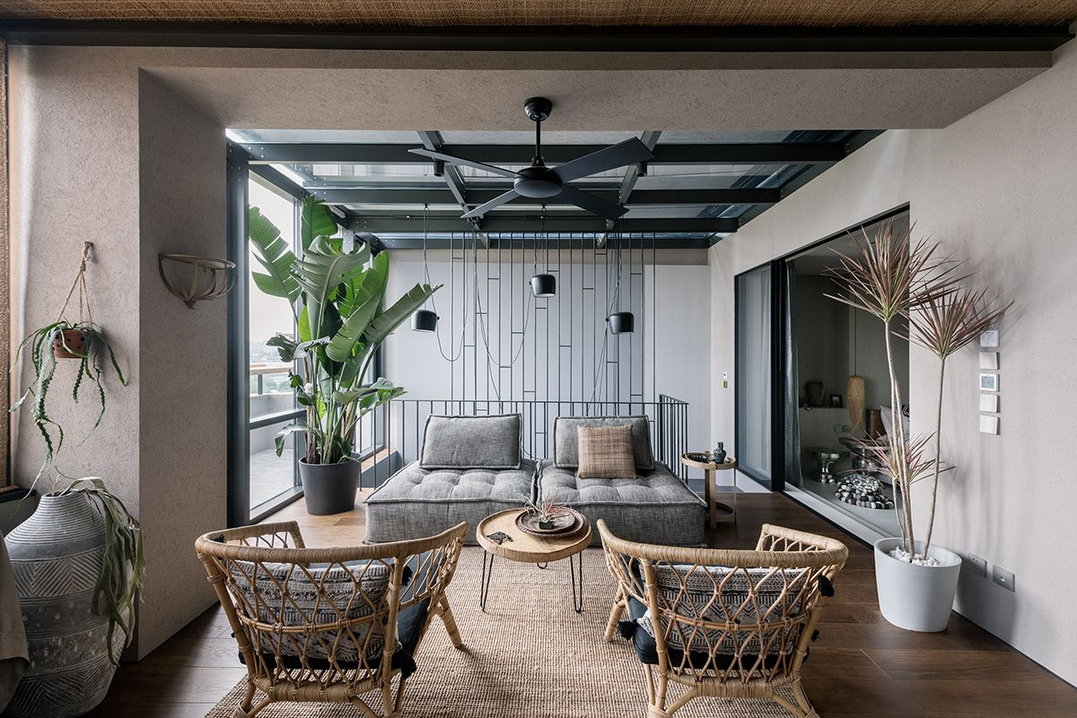 An upstairs sitting room features gray tufted seating, rattan armchairs, and large potted plants.