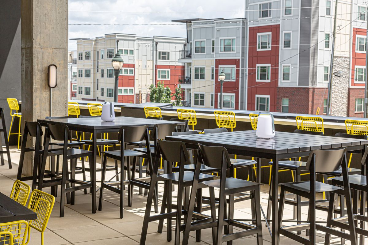 High top tables with yellow metal chairs looking toward Edgewood Avenue