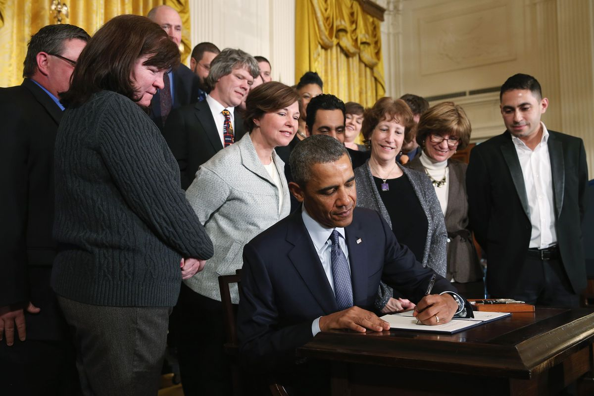 President Obama signs a presidential memorandum for overtime protections for workers during an event in the East Room at the White House, on March 13, 2014