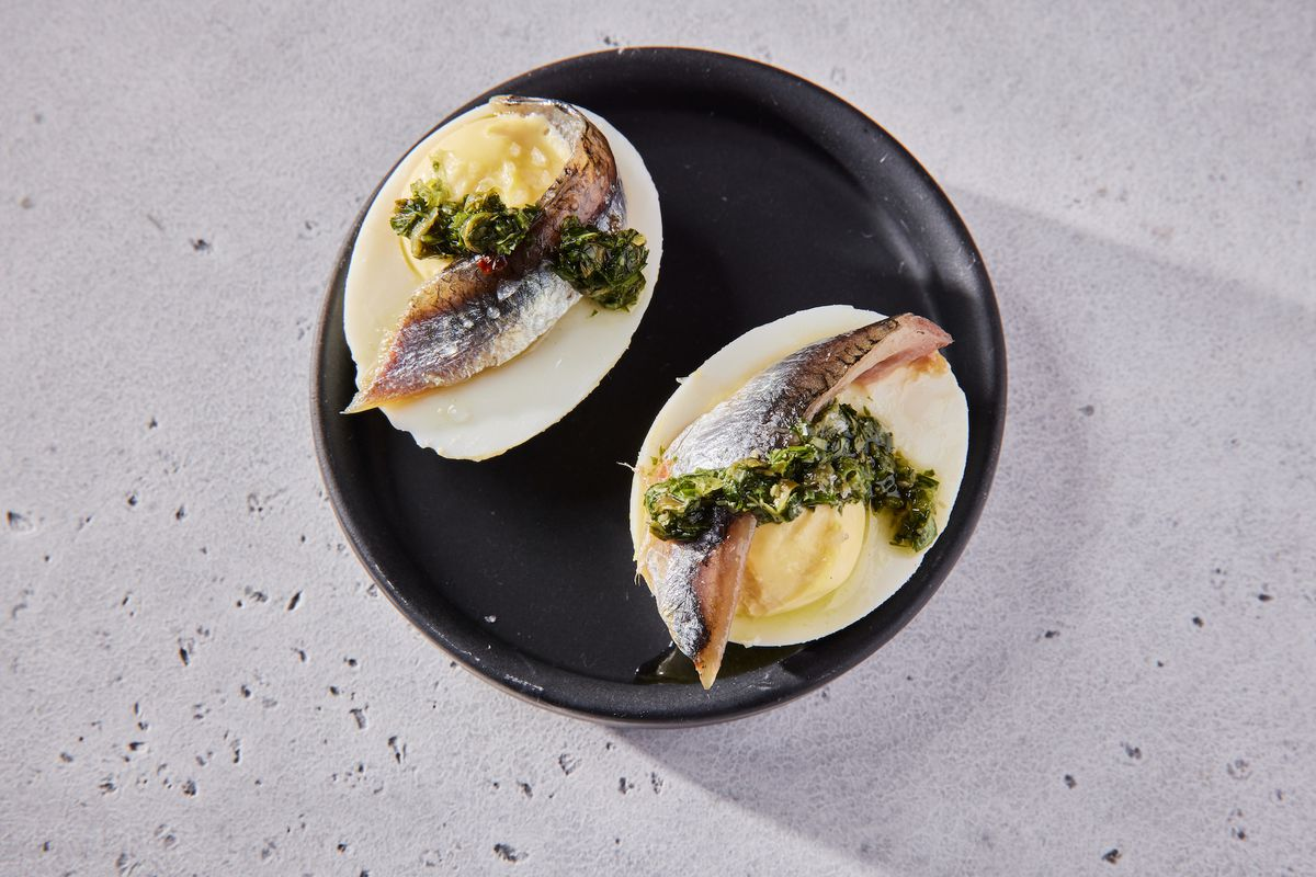 Deviled eggs topped with house cured anchovies and sals verde