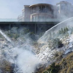 Firefighters spray foam on the hillside below a home on Viewcrest Drive in Burbank, Calif., Wednesday, June 28, 2017. Dozens of homes were under mandatory evacuation orders on the suburban edges of Burbank, where flames raced uphill through tinder-dry grass.