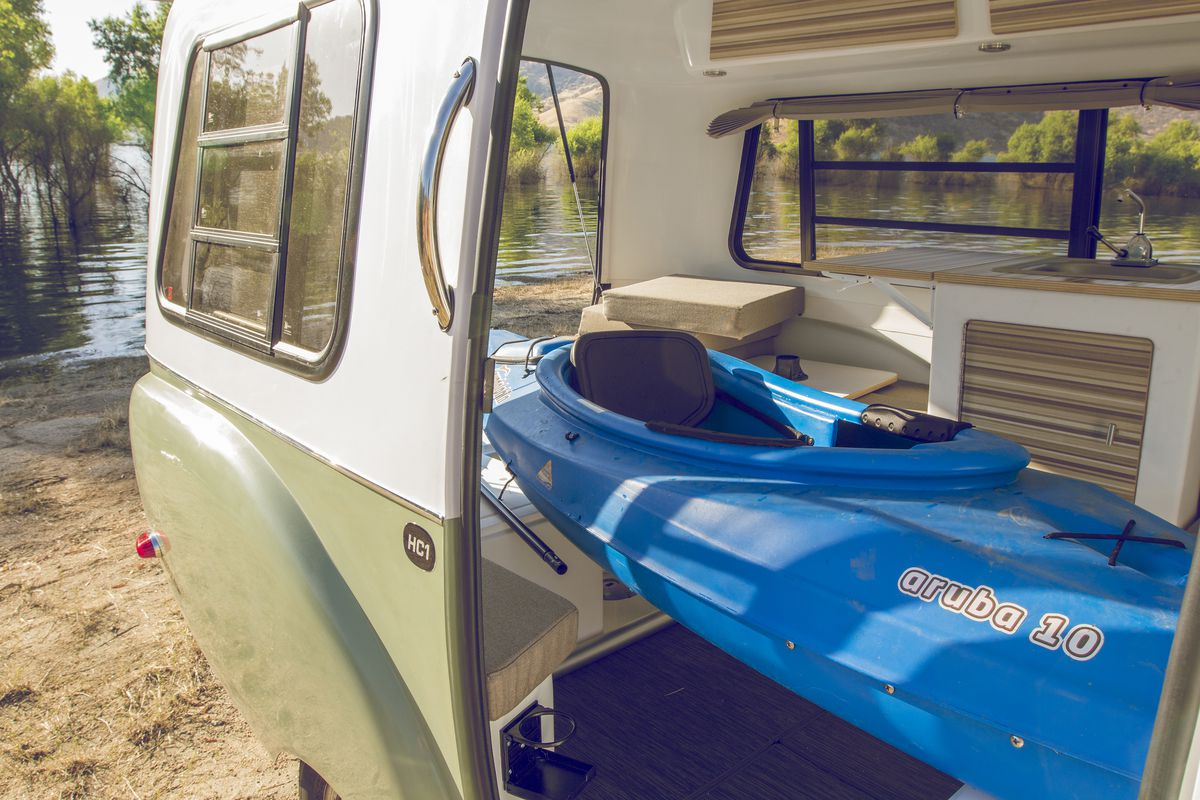A blue kayak inside of a white and green fiberglass camper.