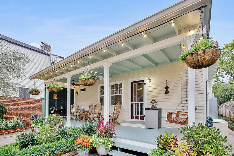 Porch with swings, rocking chairs, potted flowering plants and Edison light bulbs around the perimeter