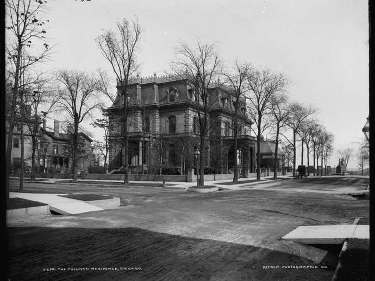 A large mansion surrounded by trees with bare branches. There is a large empty lot surrounding the trees and mansion.