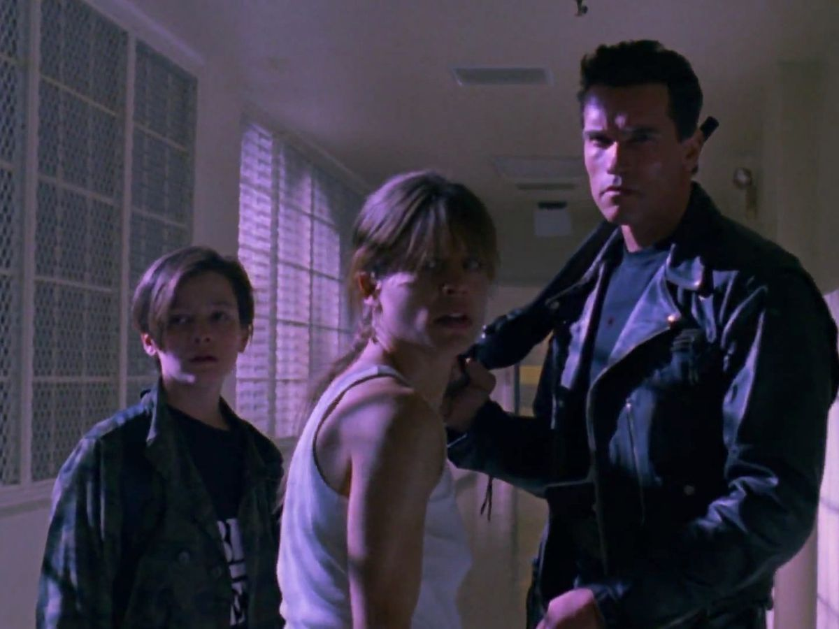 Sarah Connor, John Connor and the T-800 stand in the hallway of Pescadero State Hospital.