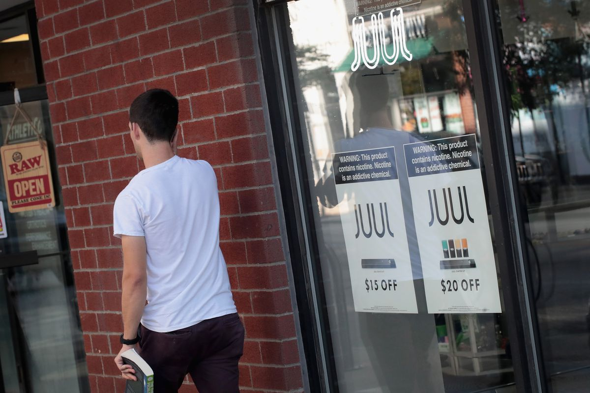 A man walks away from a store window advertising Juul e-cigarettes.