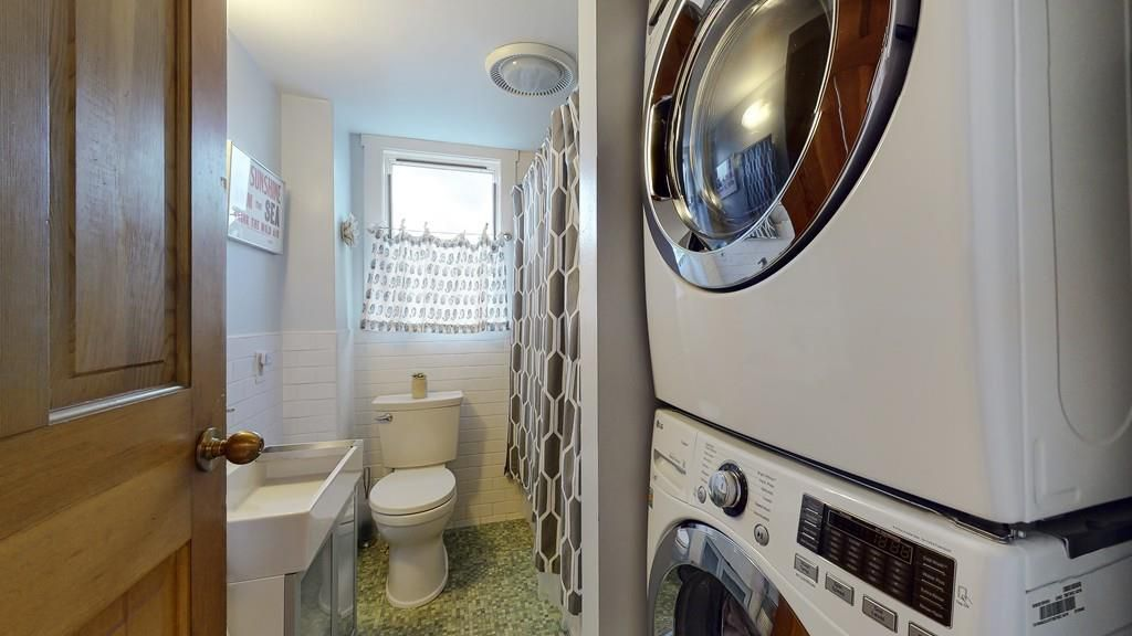 A narrow bathroom with a washer-dryer stacked next to the tub.