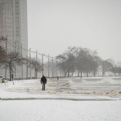A person walks along the Lakefront Trail at Oak Street Beach in the Loop, Tuesday morning, Jan. 26, 2021. Three inches of snow enveloped Chicago as the winter storm passed through northern Illinois.