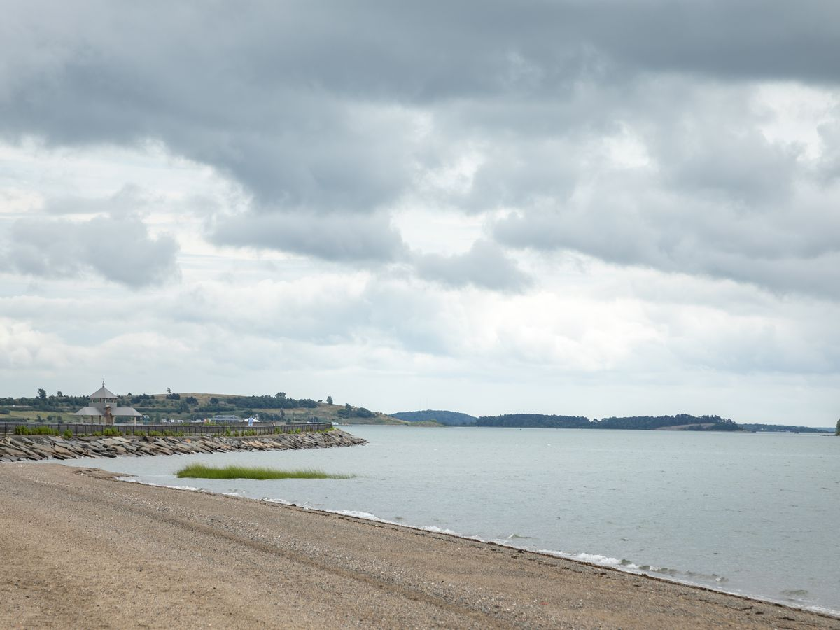 A sandy beach adjacent to a body of water. There are storm clouds in the sky.