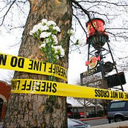 Flowers are left in police tape at Trolley Square in Salt Lake City Tuesday morning.