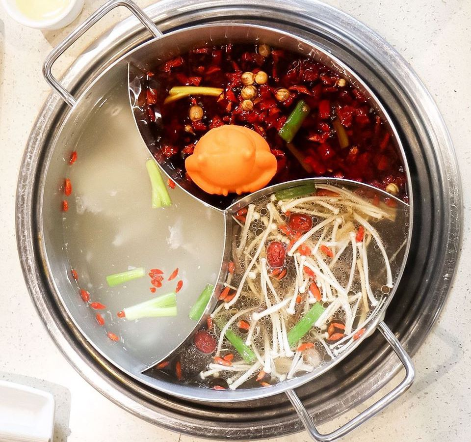 Overhead view of a metal hotpot split in three segments, holding three different soups. One is deep red and full of chiles, one is translucent and white-ish with leeks, and one is clear and packed with long, skinny, white mushrooms with tiny caps.