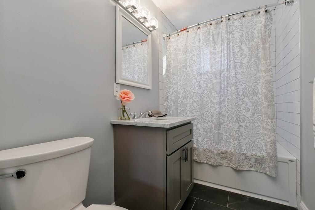 A bathroom with the curtain drawn on the shower.