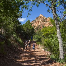 A family makes the hike back from the Kanarraville Falls on June 6, 2017  near Kanarraville, Utah.  What used to be a treasure has now become a nightmare for many Kanarraville residents. The influx of hikers has left the small community of 350 faced with many difficulties they would have never known otherwise, including parking problems and fears of contamination of the primary water source.  (Jordan Allred /The Spectrum via AP)