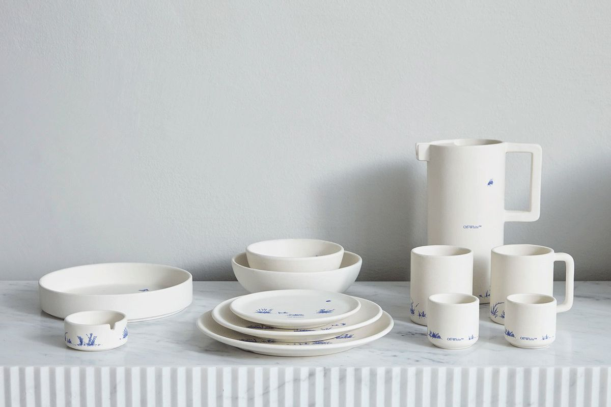 Ceramic mugs, plates, bowls, and pitcher in an off-white hue with light blue sketching of grass.
