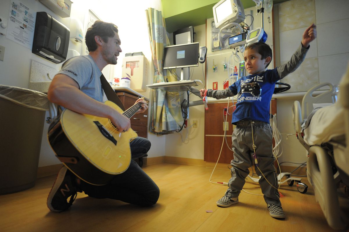 Phil Fensel volunteer musician from Musicians On Call plays for a Jonathan Fajardo (7) patient at Ann & Robert H. Lurie Children's Hospital in Chicago on Wednesday, October 9, 2019.