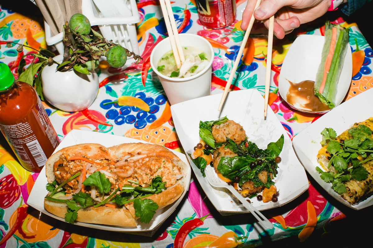 A spread of Rice Paper Scissors food — banh mi, pho, and more —on a colorful tablecloth