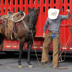 A cowboy gets out a bridle for his horse at West High School in Salt Lake City before joining Gov. Spencer Cox, first lady Abby Cox and others in driving a small herd of Texas longhorn cattle from West High School toward the Utah State Fairpark in Salt Lake City on Monday, July 19, 2021.The drive was held to celebrate the return of the Days of '47 Cowboy Games and Rodeo.