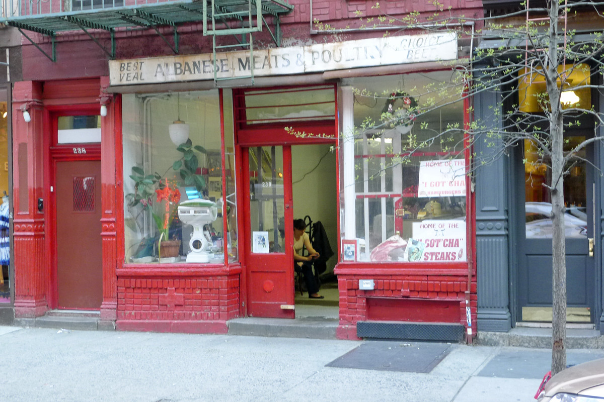 The exterior of a shop with a red frame, windows on either side, a faded sign in white up top, and pavement in front of the shop.
