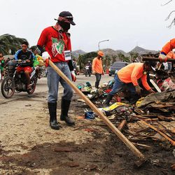 Workers clean up roads in Tacloban, Friday, Nov. 22, 2013.