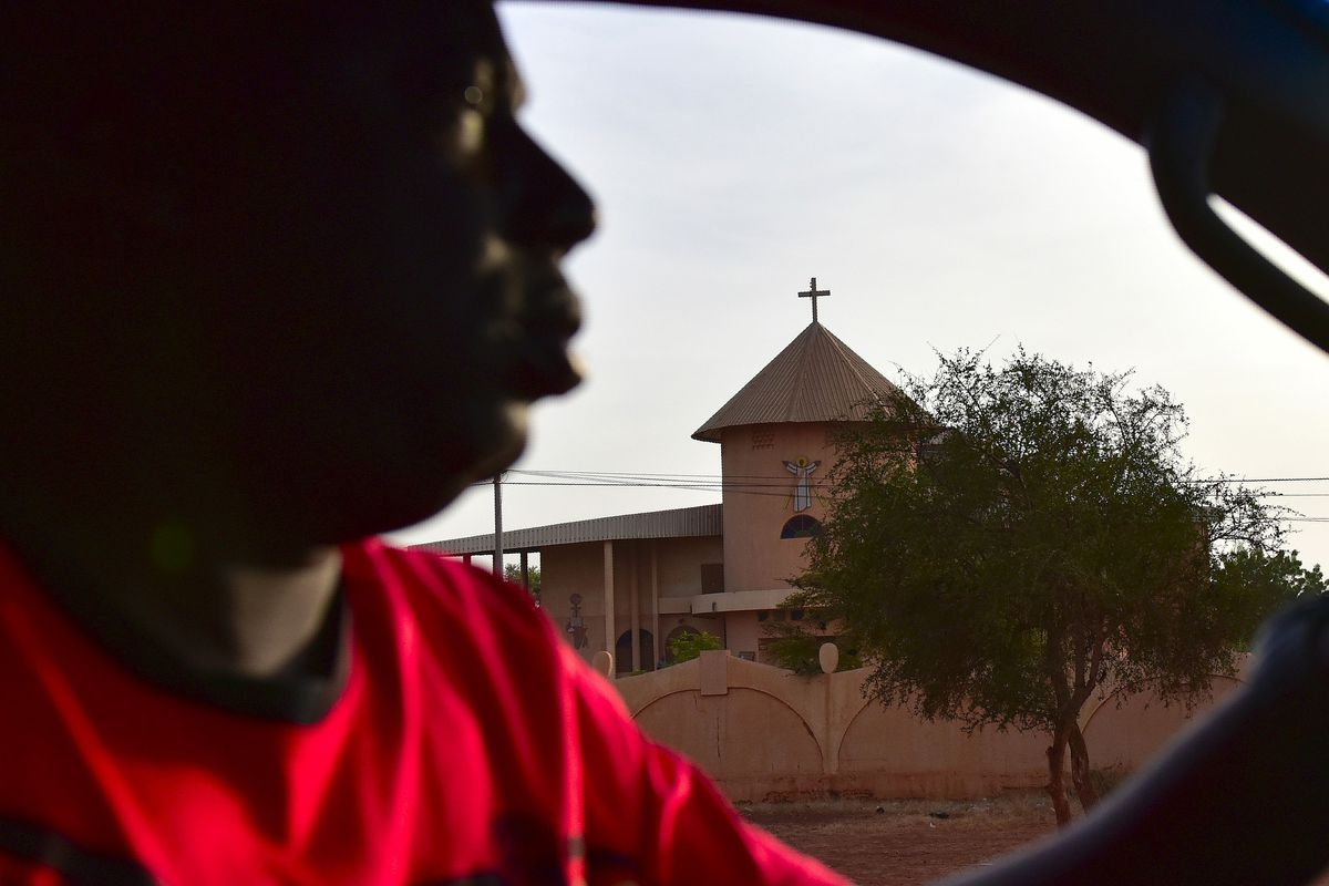 A man drives by a church in northern Bukina Faso.