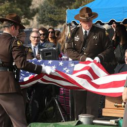 UHP troopers fold the American flag that was draped on the casket of former Utah Gov. Olene Walker during a graveside service at the Salt Lake City Cemetery in Salt Lake City on Friday, Dec. 4, 2015. Walker died of natural causes at age 85.