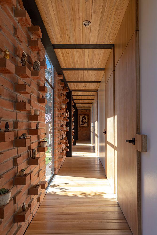 Hallway with brick wall and wood floor.