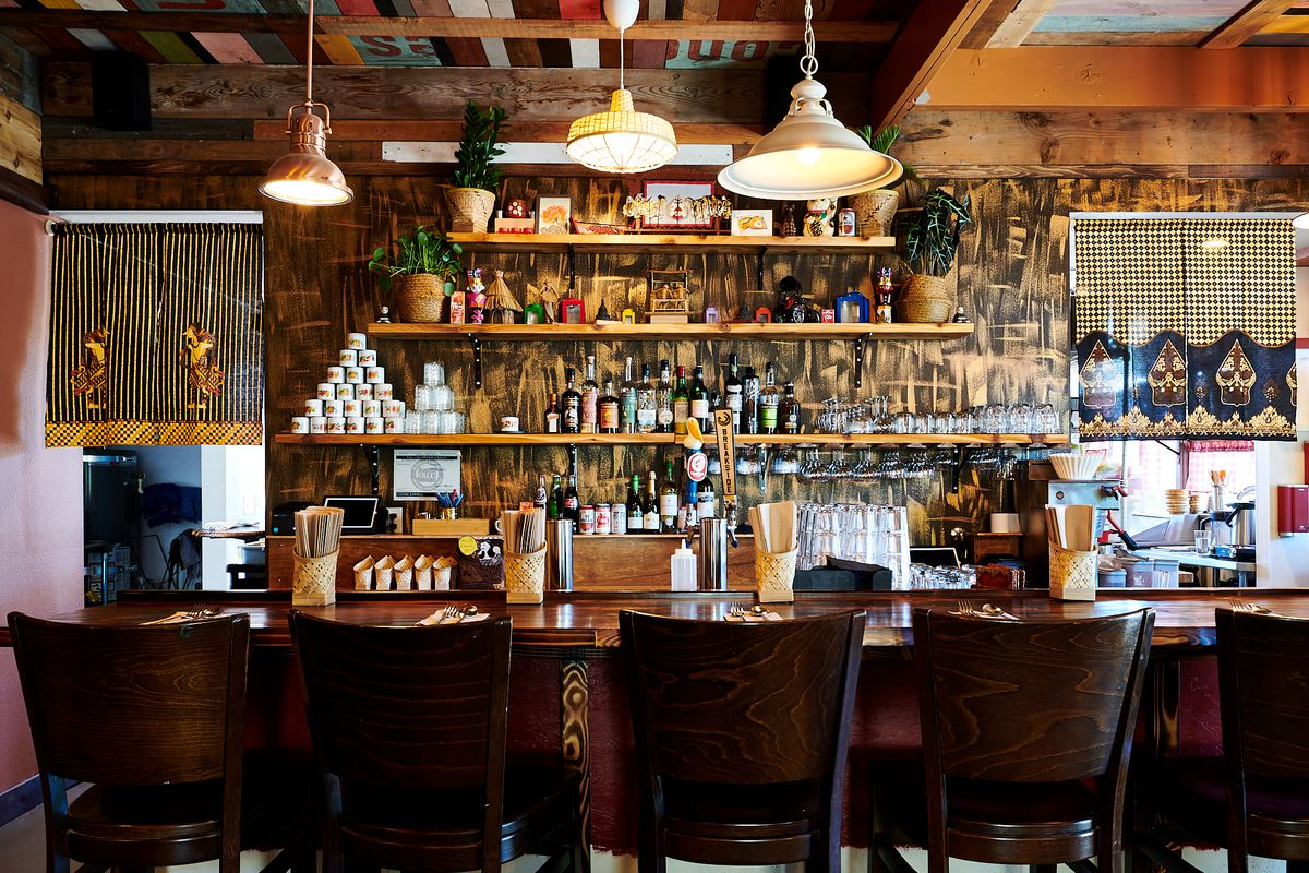 A picture of the brown-and-straw-heavy bar at Wajan, which has hanging lights, arak, and wooden stools