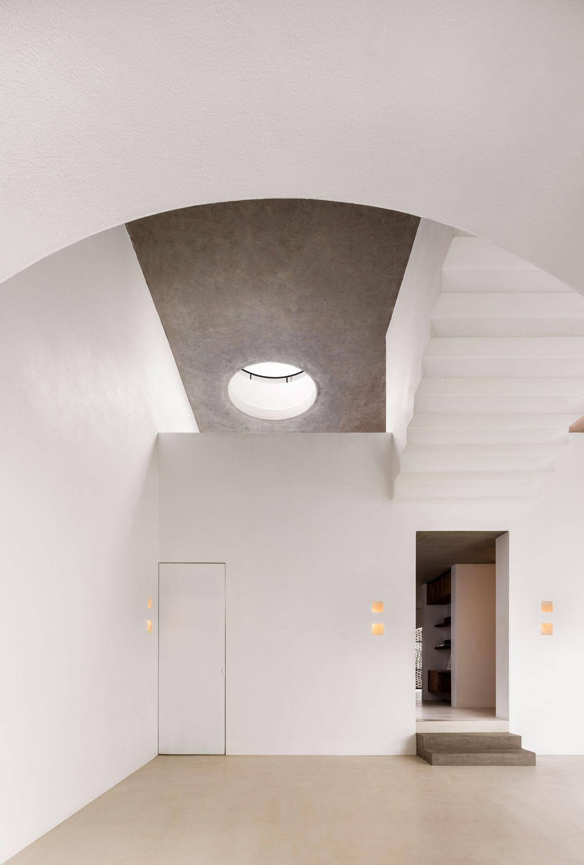 Room with circular skylight, concrete ceiling, and white walls.